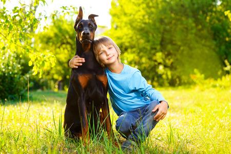 boy hugs his beloved dog or doberman in summer park.
