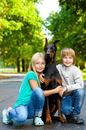 hot boy: blonde girl and boy hugs beloved dog or doberman in summer park.