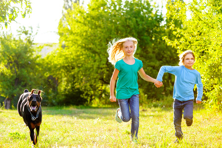 little girl smiling: boy and a girl running away from a dog or doberman in summer park. Stock Photo
