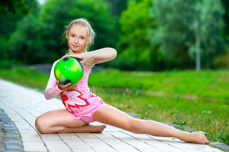costume ball: outdoor portrait of young cute little girl gymnast training with ball in park. Stock Photo