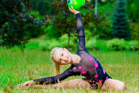 outdoor portrait of young cute little girl gymnast training with ball in park. Stock Photo