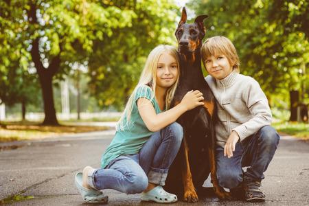 active girl: blonde girl and boy hugs beloved dog or doberman in summer park.