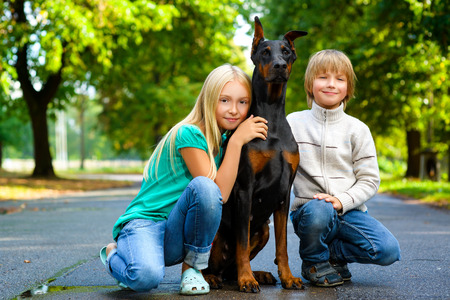 hot boy: blonde girl and boy hugs beloved dog or doberman in summer park.