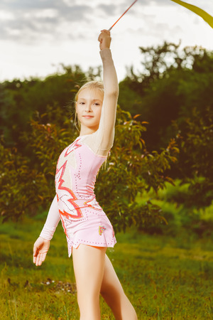 leggings: Young gymnast warms up with a gymnastic tape or feed. Stock Photo