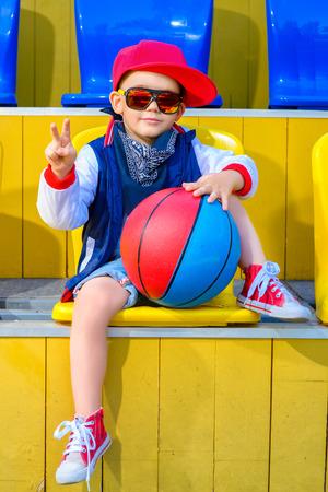 Rapper houding rap zanger hip hop danser uitvoeren. Stijlvolle kleine jongen die zich voordeed op een basketbalveld.