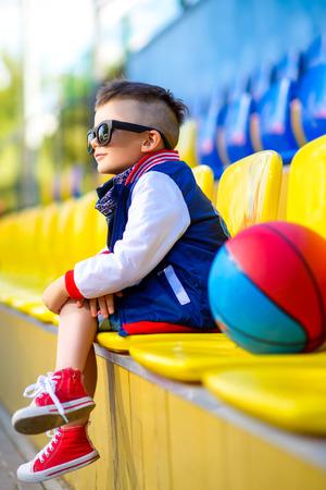 stylish boy: Rapper attitude rap singer hip Hop Dancer performing. Stylish  little boy posing at basketball court.