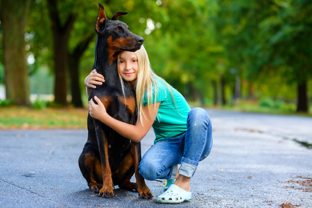 two animals: blonde girl hugs her beloved dog or doberman in summer park. Stock Photo