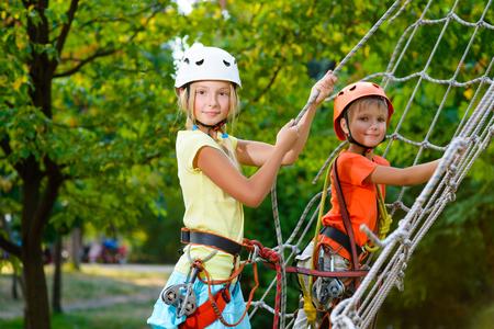niño trepando: Niños lindos. El muchacho y la muchacha que sube en una estructura de juego cuerda en el parque de aventura. Foto de archivo