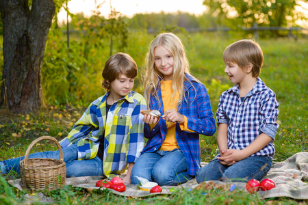 eating fruits: Happy smiling boy and girl lying together on rug. picnic in park concept.
