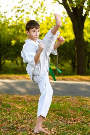 patada: chicos en el kimono blanco durante el entrenamiento de ejercicios de karate en el verano al aire libre.
