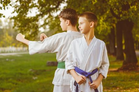 artes marciales: chicos en el kimono blanco durante el entrenamiento de ejercicios de karate en el verano al aire libre.