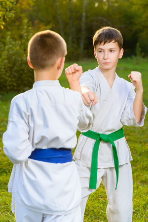 karate fighter: boys in white kimono during training karate exercises at summer outdoors. Stock Photo