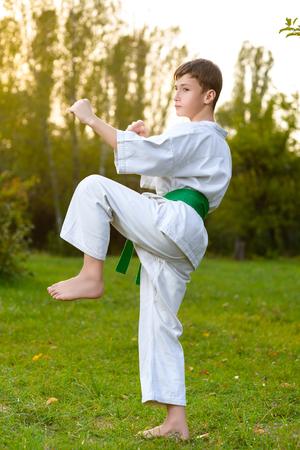 boys in white kimono during training karate exercises at summer outdoors. Stock Photo