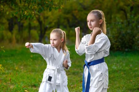 boys in white kimono during training karate exercises at summer outdoors. 免版税图像
