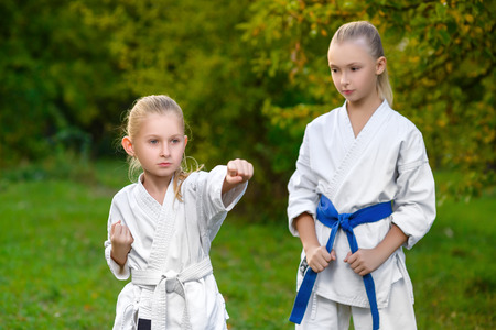 boys in white kimono during training karate exercises at summer outdoors. Standard-Bild