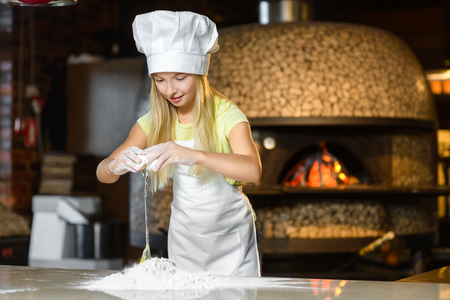 little dough: Making the dough for pizza is fun - little chef playing with flour. Stock Photo