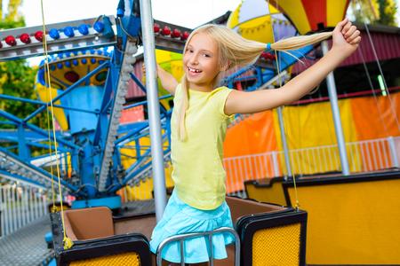 carnaval: Cute petite fille souriante chevauchant un Carnaval Carrousel au parc � th�me de l'�t�.