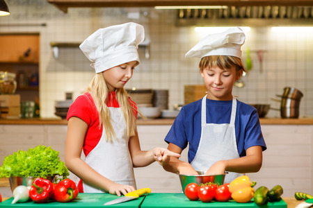 Happy smiling Chef boy and girl preparing healthy food at kitchen. the concept of vegetarianism.