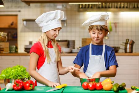 l�gumes verts: Sourire heureux chef gar�on et une fille en bonne sant� � la pr�paration des aliments cuisine. le concept de v�g�tarisme.