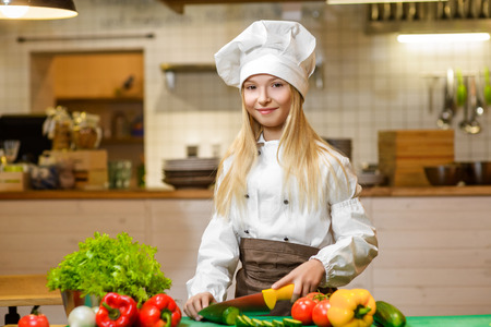 Happy smiling Chef girl preparing healthy food at kitchen. the concept of vegetarianism. Standard-Bild