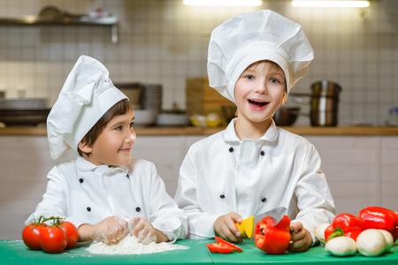 面白い幸せなシェフ男の子がレストランの厨房で調理。