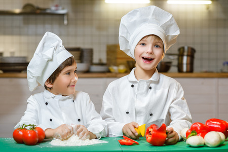 Funny happy chef boys cooking at restaurant kitchen.