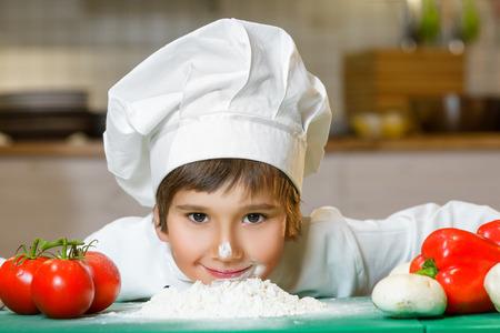 Drôle Happy Chef garçon cuisiner à la cuisine d'un restaurant et se pencha sur la farine. Banque d'images