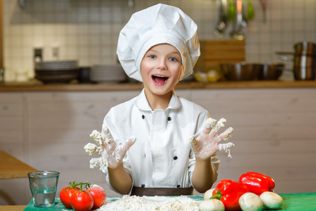 Funny happy chef boy cooking at restaurant kitchen and shows hands in the dough.