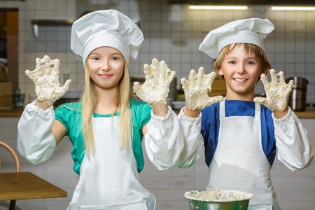dough: Divertido feliz Cocinero del niño anchura chica cocinar en la cocina del restaurante y amasar la masa en un tazón. Foto de archivo