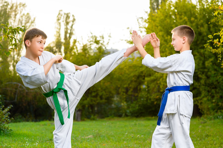 arts backgrounds: boys in white kimono during training karate exercises at summer outdoors. Stock Photo
