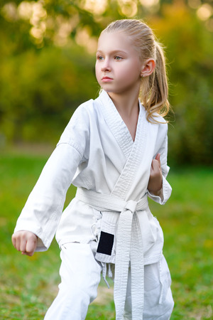 girl in white kimono during training karate exercises at summer outdoors.