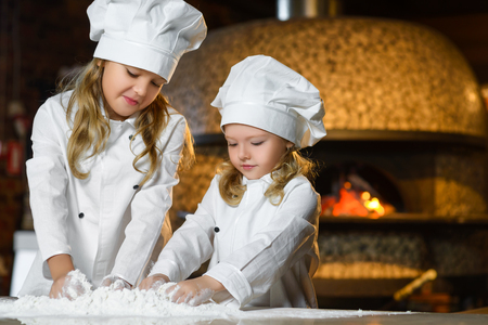 family at home: Making the dough for pizza is fun - little chefs playing with flour. Stock Photo