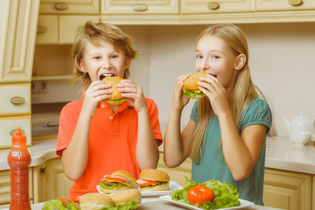 smiling happy boy and girl eating hamburgers and sandwiches. 免版税图像