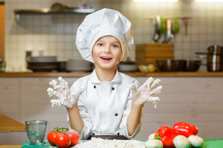 young boy smiling: Funny happy chef boy cooking at restaurant kitchen and shows hands in the dough.