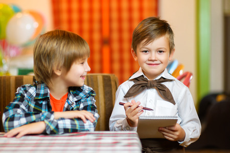 accepts: little boy waiter accepts the order in a cafe or restaurant.