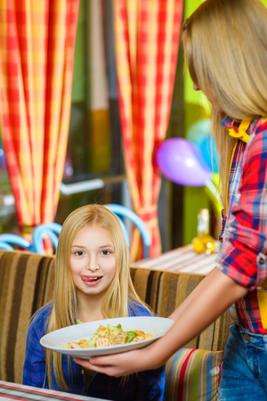 imagines: girl visitor imagines a tasty salad or delicious food awaits. Stock Photo