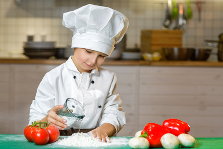 red hat: Funny happy chef boy cooking at restaurant kitchen and pours water into the dough.
