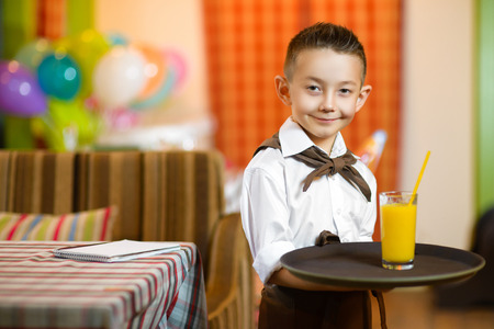 waiter: Happy cute little boy smiling waiter holding a tray width juice. Stock Photo