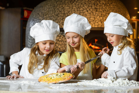 cute smiling girl chef admiring look at pizza.
