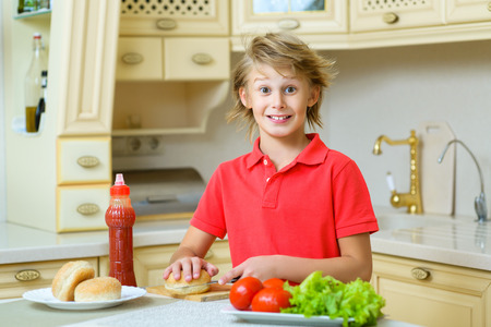 smiling boy holding a hamburger bun and salad in the kitchen. Stock Photo
