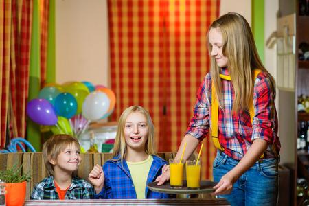 Heureux mignon souriant fille garçon tenant un plateau avec du jus. Banque d'images
