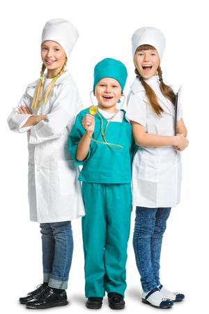 petits enfants mignons habillés comme médecin regardant la caméra avec le sourire gai isolé sur fond blanc. Concept de la médecine. Banque d'images