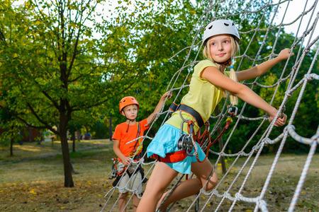 niños en recreo: Niños lindos. El muchacho y la muchacha que sube en una estructura de juego cuerda en el parque de aventura. Foto de archivo