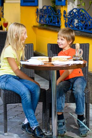 Heureux ou satisfaits largeur de fille de garçon de manger la pizza et boire du jus.