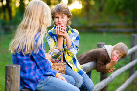 happy kids eating fruits from picnic basket outdoor. romantic or first love concept.