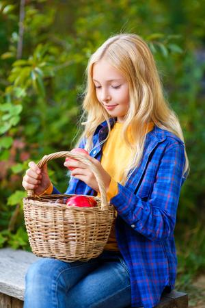 Bonne petite fille souriante tenant les pommes dans le jardin.