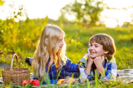 enfants heureux de manger des fruits de panier pique-nique en plein air. notion romantique ou premier amour.