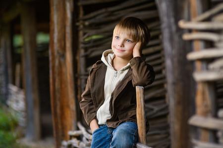 sourire garçon assis sur une clôture dans le jardin.