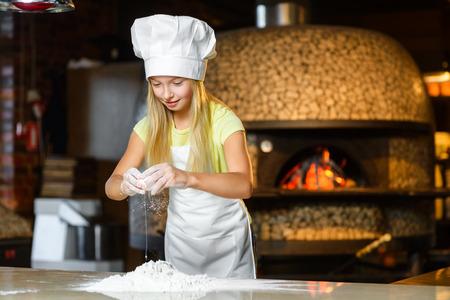 Drôle chef heureux fille de cuisine au restaurant cuisine et pétrir la pâte.