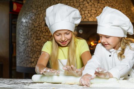 Préparation de la pâte de la pizza est amusant - petits chefs en jouant avec de la farine. Banque d'images